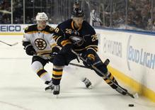 Oct 18, 2014; Buffalo, NY, USA; Buffalo Sabres center Zemgus Girgensons (28) and Boston Bruins center Carl Soderberg (34) go after a loose puck during the second period at First Niagara Center. Mandatory Credit: Timothy T. Ludwig-USA TODAY Sports