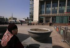 A Uighur woman looks back near exit of the South Railway Station, where three people were killed and 79 wounded in Wednesday's bomb and knife attack, in Urumqi, Xinjiang Uighur Autonomous region, May 2, 2014.  REUTERS/Petar Kujundzic