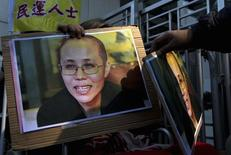 A pro-democracy protester holds a portrait of Liu Xia, the wife of jailed Nobel Peace Prize Laureate Liu Xiaobo, during a protest to call for the freeing of Chinese dissidents  outside the Chinese liaison office in Hong Kong December 5, 2013.   REUTERS/Tyrone Siu