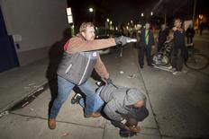 An undercover police officer, who had been marching with anti-police demonstrators, aims his gun at protesters after some in the crowd attacked him and his partner in Oakland, California December 10, 2014. REUTERS/Noah Berger