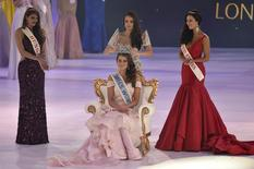 Rolene Strauss of South Africa (C) is crowned Miss World 2014 by Miss World 2013, Megan Young of the Philippines (C rear), as Elizabeth Safrit of the U.S (R) and Edina Kulczar of Hungary (L) who placed third and second respectively, look on at the ExCel Centre in east London, December 14, 2014.  REUTERS/Toby Melville