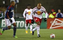 New York Red Bulls forward Thierry Henry (14) carries the ball past New England Revolution forward Teal Bunbury (10) during the second half of the Eastern Conference Championship at Gillette Stadium. Mandatory Credit: Winslow Townson-USA TODAY Sports