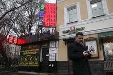 Un hombre pasa frente a un edificio con pantallas que muestran tasas de cambio en Moscú, 16 diciembre, 2014.  La fuerte subida de las tasas de interés que realizó el lunes el banco central ruso no lograba aliviar la presión sobre el rublo el martes, dado que el mercado seguía poniendo a prueba la resolución del organismo para defender a la moneda y presionaba a la debilitada economía rusa. REUTERS/Maxim Zmeyev
