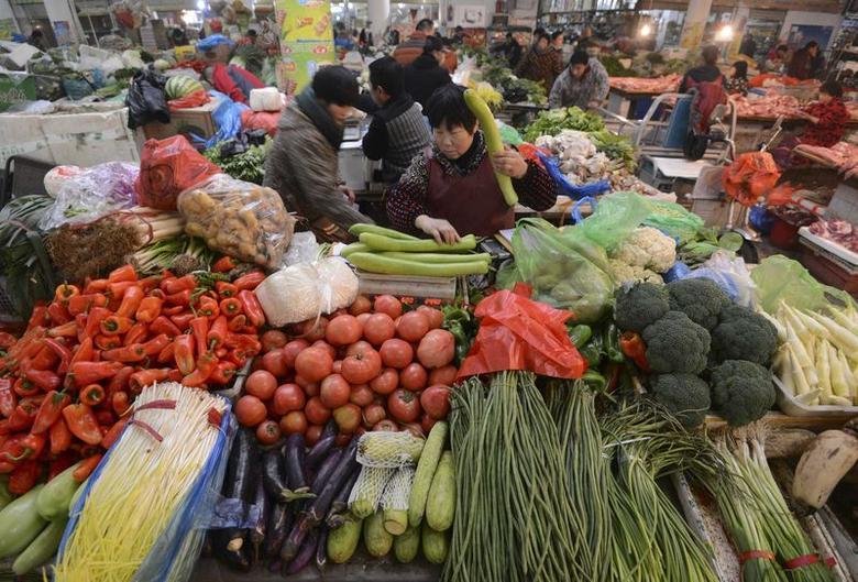 A vendor (C) weighs vegetable at a market in Fuyang, Anhui province December 10, 2014.  REUTERS/Stringer