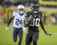 Jacksonville Jaguars running back Jordan Todman (30) is pursued by Tennessee Titans cornerback Coty Sensabaugh (24) on a 62-yard touchdown run in the fourth quarter at EverBank Field. The Jaguars defeated the Titans 21-13. Mandatory Credit: Kirby Lee-USA TODAY Sports