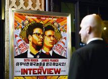 """Un guardia de seguridad frente a un afiche de la película """"The Interview"""" publicado en la entrada del cine United Artists en Los Angeles, dic 11 2014. Estados Unidos dijo el jueves que el ciberataque contra Sony Pictures, del que se acusa a Corea del Norte, es un asunto grave de seguridad nacional y que el Gobierno estudia una respuesta proporcional.  REUTERS/Kevork Djansezian"""
