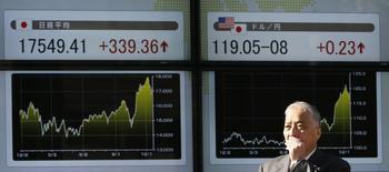 Мужчина проходит мимо экрана с котировками в Токио 19 декабря 2014 года. Курс доллара к иене поднялся до двухнедельного максимума, после чего замедлил рост при пониженной активности на рынке в отсутствие японских игроков. REUTERS/Issei Kato