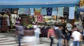 Personas caminan frente a un local comercial en una calle en el centro de Sao Paulo. Imagen de archivo, 4 diciembre, 2014.  La confianza del consumidor en Brasil permaneció cerca de mínimos niveles en seis años en diciembre, pese a una leve mejoría el mes previo, según un sondeo privado publicado el martes. REUTERS/Paulo Whitaker