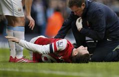 Jogador do Arsenal Koscielny recebe atendimento após sofrer lesão em jogo do Campeonato Inglês contra o Manchester City. 14/12/2014 REUTERS/Phil Noble