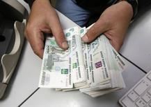 Un empleado cuenta rublos al interior de una oficina privada en Krasnoyarsk, Rusia, dic 17 2014. El rublo subió el martes a un máximo de dos semanas impulsado por medidas de control de capital informales tomadas para evitar que se repita la inflación y las protestas que marcaron la crisis financiera de Rusia en 1998. REUTERS/Ilya Naymushin