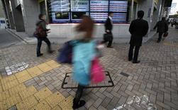 Un hombre observa una pantalla electrónica que muestra el índice Nikkei y la tasa de cambio del yen versus el dólar en Tokio, 24 diciembre, 2014. Las bolsas de Asia subían y el dólar se fortalecía el miércoles gracias a unos datos que revelaron un crecimiento económico sorprendentemente robusto de Estados Unidos, lo que apoyaba la confianza de los inversores luego de la turbulencia de las últimas dos semanas. REUTERS/Yuya Shino