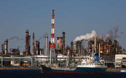 Судно проходит мимо промышленного комплекса в Кавасаки 18 декабря 2014 года. Цены на нефть растут за счет улучшения экономических показателей США, но завершат снижением пятую неделю подряд. REUTERS/Thomas Peter