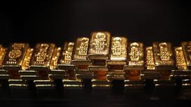 Золотые слитки в сейфе ProAurum в Мюнхене 6 марта 2014 года. Цены на золото растут на фоне снижения курса доллара к корзине основных валют, но рынок готовится завершить вторую неделю подряд в минусе. REUTERS/Michael Dalder