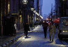 Personas caminan por el distrito financiero de Buenos Aires durante la noche. Imagen de archivo, 1 agosto, 2014. Argentina estima que reducirá en 1.100 millones de dólares su déficit energético el año próximo debido a la caída del precio internacional del crudo y al aumento de la producción local, dijo el martes el Jefe de Gabinete, Jorge Capitanich. REUTERS/Marcos Brindicci