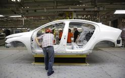 Workers prepare to assemble parts of a Volvo car at an assembly line of the new Volvo automobile manufacturing plant in Chengdu, Sichuan province, June 5, 2013.  REUTERS/Jason Lee