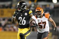 Pittsburgh Steelers running back Le'Veon Bell (26) runs the ball past Cincinnati Bengals linebacker Vincent Rey (57) in the first half at Heinz Field. Jason Bridge-USA TODAY Sports