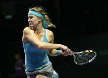 Eugenie Bouchard of Canada follows through on a return to Ana Ivanovic of Serbia during their WTA Finals singles tennis match at the Singapore Indoor Stadium October 22, 2014. REUTERS/Edgar Su