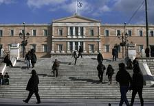 People make their way in central Syntagma Square as the parliament building is pictured in the background in Athens January 6, 2015. REUTERS/Alkis Konstantinidis