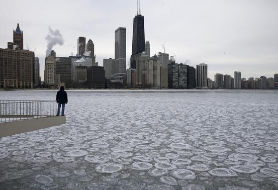 Charles Martinez looks over the partially frozen Lake Michigan and the Chicago skyline, January 5, 2015.  REUTERS-Jim Young