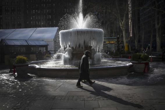 A man walks past the ice-covered Josephine Shaw Lowell Memorial Fountain, in frigid temperatures in Bryant Park in Manhattan, January 8, 2015.  REUTERS-Mike Segar