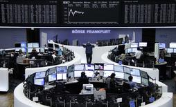 Traders are pictured at their desks in front of the German share price index DAX board at the Frankfurt stock exchange on December 22, 2014.  REUTERS/Remote/Pawel Kopczynski