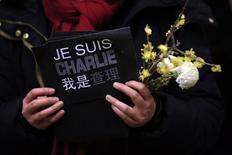 Mulher segura cartaz em homenagem a vítimas de ataque a jornal Charlie Hebdo em Paris, durante cerimônia em Xangai. 09/01/2015 REUTERS/Aly Song