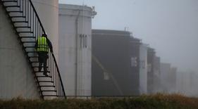Рабочий спускается по лестнице на НПЗ Total в Гранпюи под Парижем 6 января 2015 года. Цены на нефть снижаются, так как банк Goldman Sachs понизил краткосрочный прогноз цен, а спрос в США сократился из-за пожаров на двух НПЗ. REUTERS/Christian Hartmann