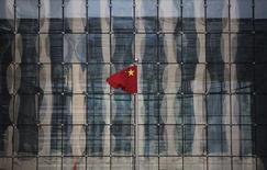 Una bandera nacional de China frente a un banco comercial en una calle financiera, Beijing. Imagen de archivo, 24 noviembre, 2014. Los bancos chinos ofrecieron mucho menos crédito que lo esperado en diciembre a pesar de un sorpresivo recorte en las tasas de interés del banco central, lo que llevó a las empresas hacia la banca informal en un duro golpe a los esfuerzos de reforma financiera del Gobierno. REUTERS/Kim Kyung-Hoon