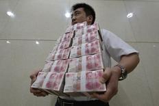 Работник банка несет пачки юаней. Тайюань, провинция Шаньси, 4 июля 2013 года. Китай в пятницу объявил о новых мерах поддержки экономики после того, как стало известно о сокращении банковского кредитования и иностранных инвестиций. REUTERS/Jon Woo