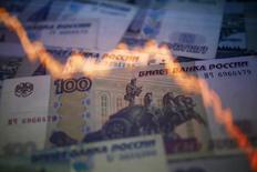 График динамики курса пары доллар/рубль на фоне российских банкнот. Варшава, 7 ноября 2014 года. Международное рейтинговое агентство Moody's снизило рейтинг госдолга России до Baa3 с Baa2, предупредив, что ослабление рубля и падение цен на нефть подрывают и без того невысокие перспективы экономического роста страны. REUTERS/Kacper Pempel