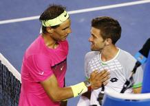 Rafael Nadal (L) of Spain consoles Tim Smyczek of the U.S. after their men's singles second round match at the Australian Open 2015 tennis tournament in Melbourne January 21, 2015. REUTERS/Athit Perawongmetha