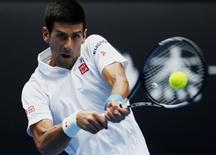 Novak Djokovic of Serbia hits a return to Andrey Kuznetsov of Russia during their men's singles second round match at the Australian Open 2015 tennis tournament in Melbourne January 22, 2015. REUTERS/Issei Kato