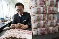Работник отделения банка China Construction Bank считает юани. Наньтун, провинция Цзянсу, 2 декабря 2014 года. Китайские банки испытывают давление из-за растущего объема плохих долгов, однако ситуация под контролем, сообщил регулятор, добавив, что западные санкции к России не несут вреда Китаю. REUTERS/China Daily