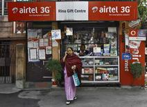 A woman speaks on her mobile phone after recharging it at a local stationary cum prepaid mobile recharge shop in Kolkata January 19, 2015. REUTERS/Rupak De Chowdhuri