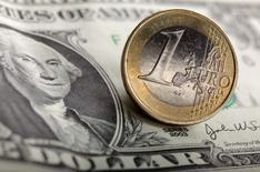 Монета в 1 евро и купюра в 1 доллар США в Варшаве 18 января 2011 года. Курс евро к доллару упал до 11-летнего минимума после победы на парламентских выборах в Греции партии Syriza, выступающей против жесткой экономии государственных средств и условий получения иностранных кредитов. REUTERS/Kacper Pempel