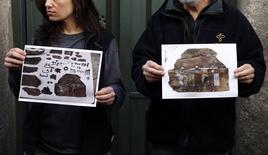 Forensic expert Francisco Etxeberria (R) and archaeologist Almudena Garcia Rubio hold pictures showing the remains of niches, one of them appeared with the letters M.C. on it,  found in the crypt of Trinitarian convent as they pose outside the convent in Madrid January 26, 2015. REUTERS/Sergio Perez