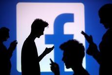 Pessoas posam usando celulares em frente ao logo do Facebook para foto de ilustração. 29/10/2014 REUTERS/Dado Ruvic