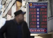 Мужчина у пункта обмена валюты в Алма-Ате. 14 января 2015 года. Нацбанк Казахстана тратит резервы ради стабильности национальной валюты на фоне обещаний властей не допустить новой девальвации, в то время как эксперты говорят, что из-за низких цен на нефть обесценение тенге неизбежно. REUTERS/Shamil Zhumatov