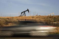 Машина проезжает мимо станков-качалок в Бейкерсфилде, Калифорния 18 января 2015 года. Цены на нефть снижаются за счет укрепления доллара на торгах в Азии и значительного повышения запасов нефти в США. REUTERS/Lucy Nicholson