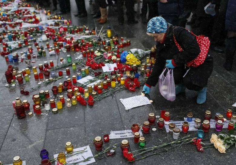 A woman lights a candle during a rally in memory of people who died during shelling in the southern Ukrainian city of Mariupol on Saturday, in Kiev January 25, 2015. Pro-Russian rebels launched an offensive against the strategic port of Mariupol in eastern Ukraine on Saturday, prompting the European Union's foreign policy chief to warn of a further ''grave deterioration'' in EU-Russian relations. Mariupol's city administration said the rebels had killed at least 30 people and injured 83 others by firing rockets from long-range GRAD missile systems.  REUTERS/Gleb Garanich  (UKRAINE - Tags: POLITICS CIVIL UNREST CONFLICT)