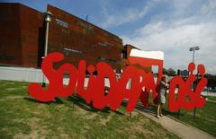 A woman stands next to a Solidarity logo in front of the newly open European Solidarity Centre during the 34th anniversary of emerging Solidarity trade union at the historic shipyard area in Gdansk, northern Poland in this August 31, 2014 file photograph. REUTERS/Kacper Pempel/Files