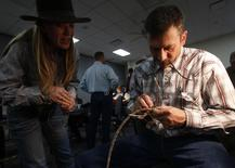 Doug Groves (R) teaches a rawhide braiding workshop at the 31st National Cowboy Poetry Gathering in Elko, Nevada January 28, 2015.   REUTERS/Jim Urquhart