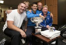 Novak Djokovic (C) of Serbia poses with his coach Boris Becker (R), members of his support team and the men's singles trophy in the player's locker room after he defeated Andy Murray of Britain at the Australian Open tennis tournament February 2, 2015, in this handout courtesy of Tennis Australia.   REUTERS/Fiona Hamilton/Tennis Australia/Handout via Reuters