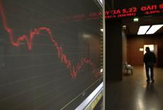 A man walks inside Athens stock exchange as a monitor shows the general index January 28, 2015. REUTERS/Alkis Konstantinidis