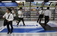 People walks on a floor advertising poster of Sony Corp's PlayStation 4 console at an electronics retail store in Tokyo July 16, 2014. REUTERS/Yuya Shino