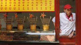 Продавец палатки, торгующей едой, в Пекине. 6 мая 2013 года. Сектор услуг Китая рос в январе самыми медленными темпами за полгода, показало частное исследование, укрепив ожидания того, что регуляторы могут ввести новые стимулы, чтобы предотвратить резкое замедление второй мировой экономики. REUTERS/Kim Kyung-Hoon