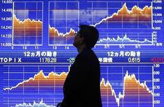 Мужчина у брокерской конторы в Токио. 25 октября 2013 года. Азиатские фондовые рынки, кроме Гонконга, снизились в четверг из-за решения Европейского центробанка не принимать греческие облигации в качестве залога. REUTERS/Yuya Shino