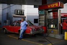 A man fills up his 1976 Chevy Nova with gasoline at a PDVSA gas station in Caracas January 12, 2015. REUTERS/Jorge Silva