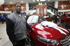 Detroit resident James Robertson reacts next to the 2015 red Ford Taurus sedan he was surprised with as a free gift at the Suburban Ford dealership in Sterling Heights, Michigan, February 6, 2015.  REUTERS/Rebecca Cook