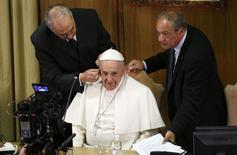 Pope Francis is helped with earplugs as he arrives to lead a meeting for the 4th World Congress of Educational Scholas Occurrentes in the Synod hall at the Vatican February 5, 2015.  REUTERS/Max Rossi
